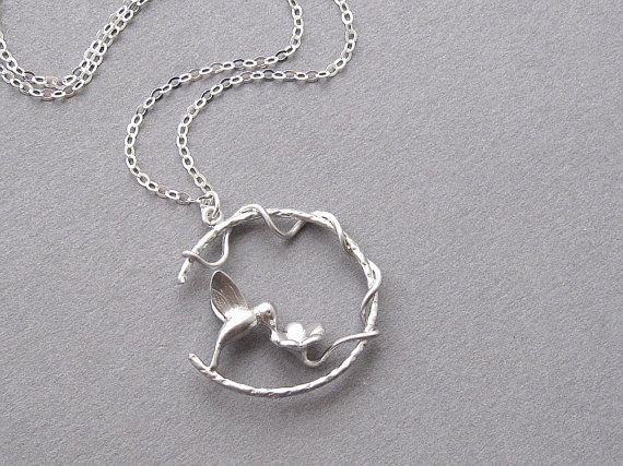 Hummingbird necklace with a little bird in a loop sipping nectar from a flower. Bird and flower loop is plated in matte rhodium and strung on a fine