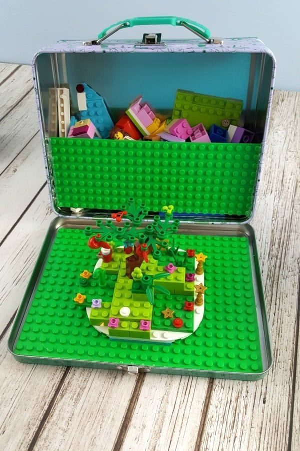Great DIY gift! Make road trips and waiting rooms more fun by bringing along travel toys. Check out this tutorial for making your own LEGO travel case using an inexpensive metal lunchbox and a LEGO base plate. Your kids will love this fun set! #LEGO #Travel #BoredomBuster
