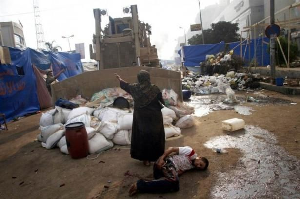 A woman defends a wounded protester from a military bulldozer [Egypt, 2013]