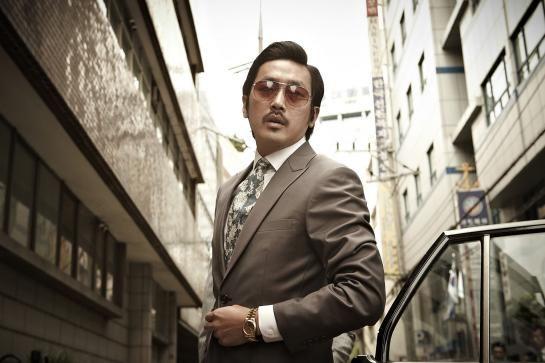 """""""Nameless Gangster"""" - Años 80. Ik-hyun (Choi Min-sik), un funcionario de aduanas corrupto, está a punto de ser despedido. Al intentar dar el último golpe, vendiendo una bolsa de heroína, entra en contacto con un importante jefe mafioso de Busan. Enseguida se gana su confianza, y los dos unidos llegan a convertirse en los amos de la ciudad. Pero, cuando en los años 90 el gobierno declara la guerra abierta contra el crimen organizado, empiezan a aparecer grietas en su relación. (FILMAFFINITY)."""