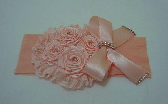 Faixa em meia de seda salmon com flores e laço em fita com detalhes dourados para deixar sua princesa encantada. R$ 14,90
