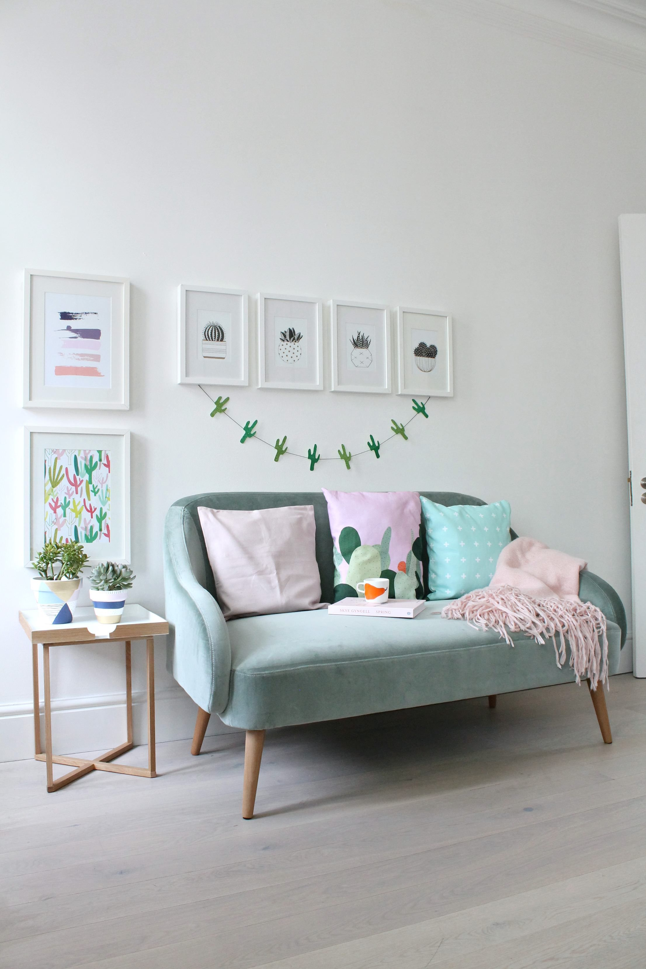 Sage green velvet sofa and all things pink, gold and cacti.