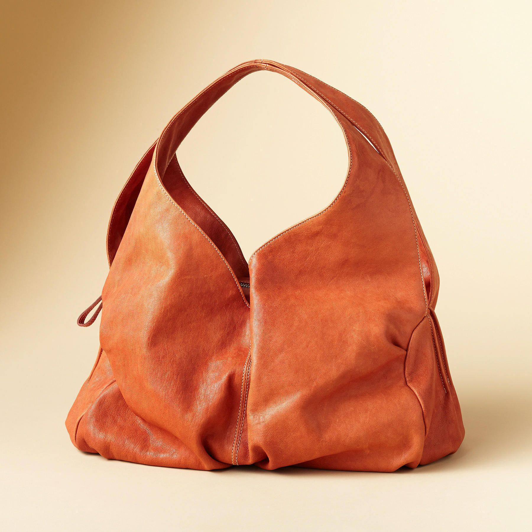 """PLENTITUDE OF POCKETS BAG--Our bag is a plethora of pouches—four open exterior pockets span the sides for close-at-hand storage of cell phone and such. The equally commodious main compartment zips shut, fully lined with pockets on both sides. Made in Italy of soft sheepskin leather. Approx. 13-1/2""""W x 5""""D x 7""""H."""