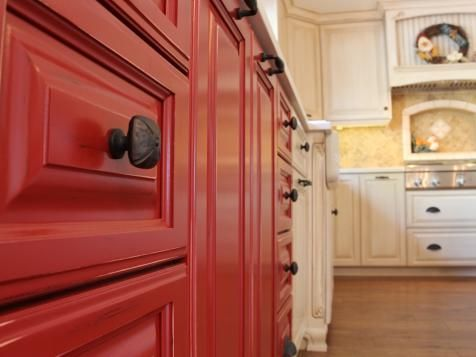 red kitchen cabinets with oil-rubbed bronze drawer knobs make for a