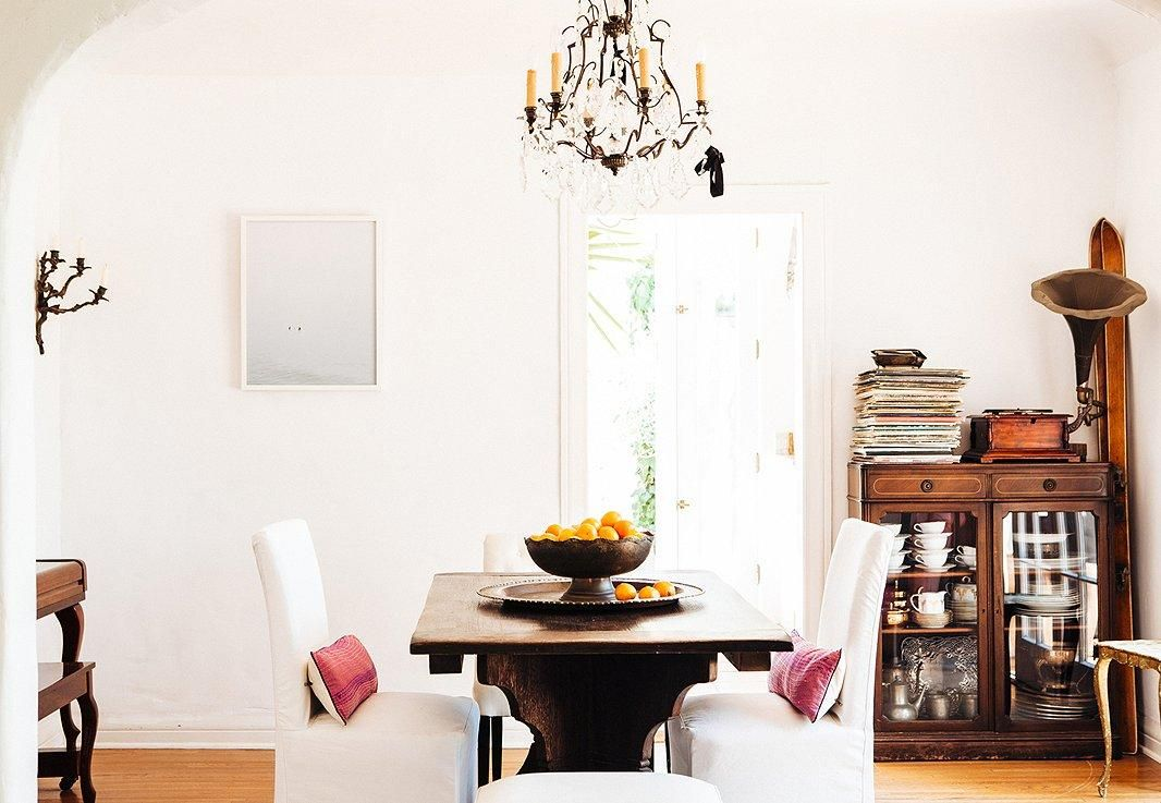 Heidi Merrick Shares Her Secret Sources -- Read more on our Style Guide! Her midcentury modern dining room with solid wood furniture and slipcovered dining chairs gets a hacienda vibe from a wrought iron chandelier, warm tones, and a vintage sterling silver collection on display in a glass front cabinet.