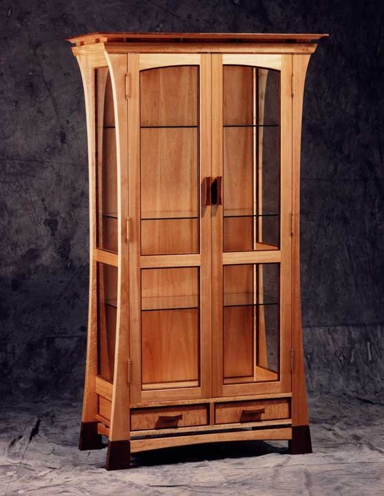 Curio Cabinet  A tall and skinny cabinet with glass doors and panels that  is used. Curio Cabinet  A tall and skinny cabinet with glass doors and