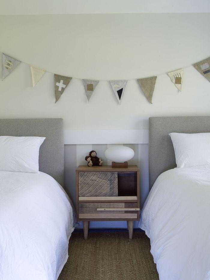 Gästrum i vitt och beige. Påslakan i bomull, sänggavel i linne och på väggarna marina vimplar.