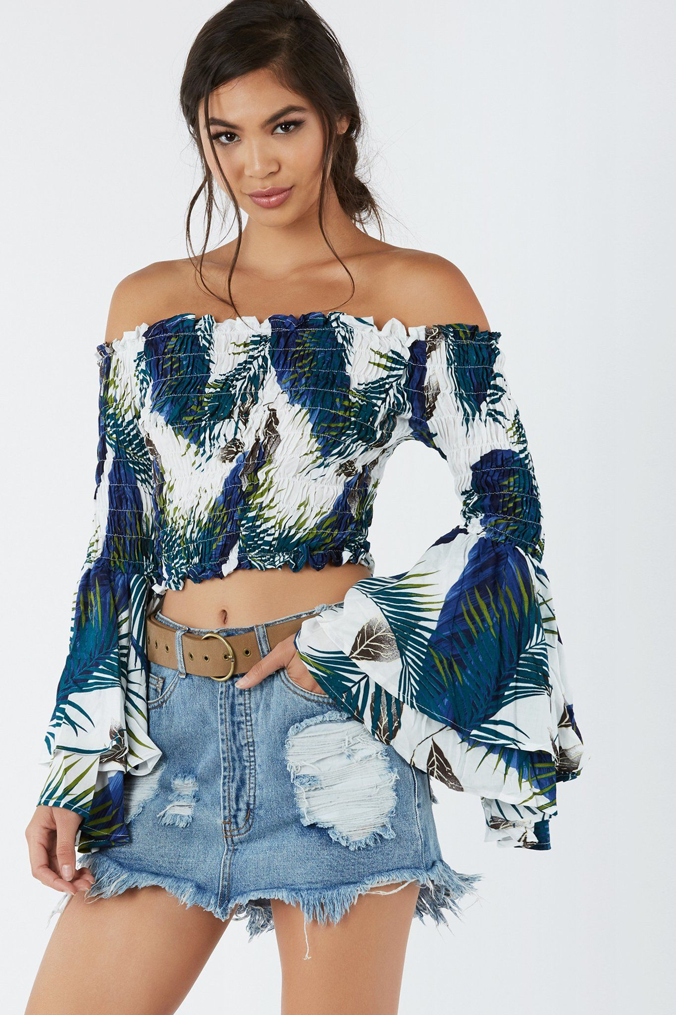 Fun off shoulder top with flowy bell ruffled sleeves. Tropical print throughout with elasticized fit and cropped hem finish.