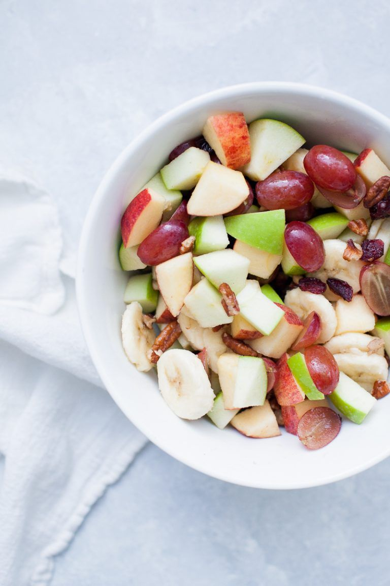 white bowl with creamy whipped cream topped fruit salad