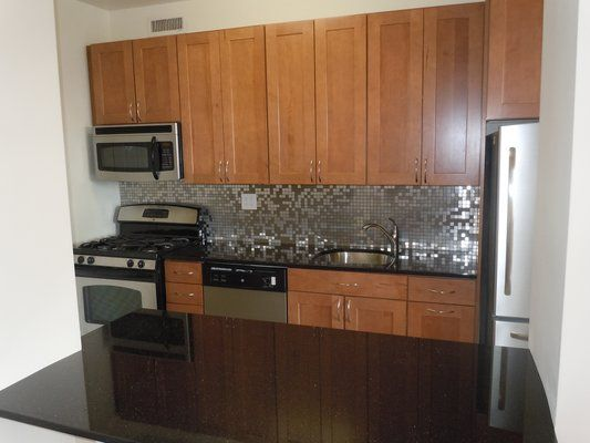 with dark countertops cabinets stainless backsplash black