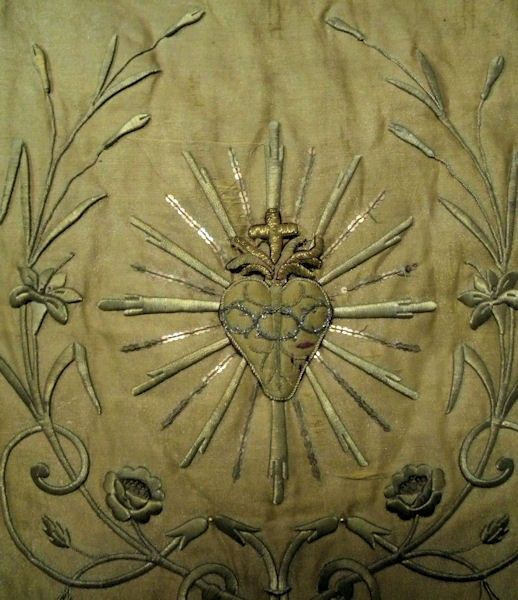 It is an early to mid 19thc vestment, featuring a couched and embroidered sacred heart applique with gold spangles all around it dance on the cloth of gold ground..there are gorgeous rose and floral padded, metallic appliques in the background with long, luxurious gold metallic (the real deal here) bullion fringe hanging from the bottom..and the most unique gold metallic torchon lace along the edges of the entire banner..