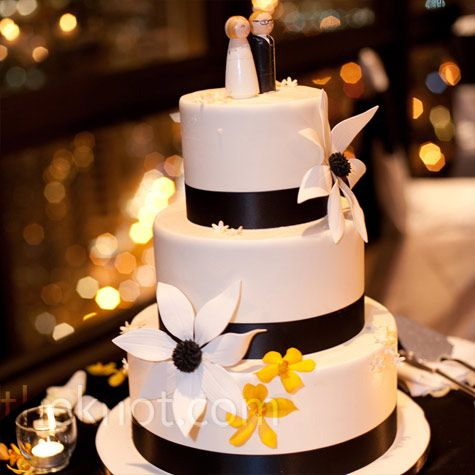Black ribbon trim and a mix of fresh and sugar flowers decorated the three-tiered cake, and the wooden topper resembled the newlyweds.