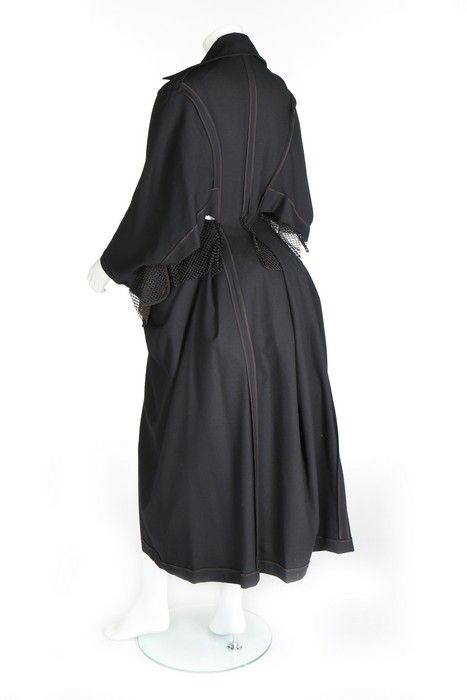 Yohji Yamamoto black wool 'bustle' ensemble, automn/winter 1995. size S, of black wool, pres-stud fastened down the front, with visite-style underarm openings, 3 mesh-lined pleats to the rear skirt, complete with black nylon mesh petticoat with can be worn internally or externally with waist ties. £1500-£2500