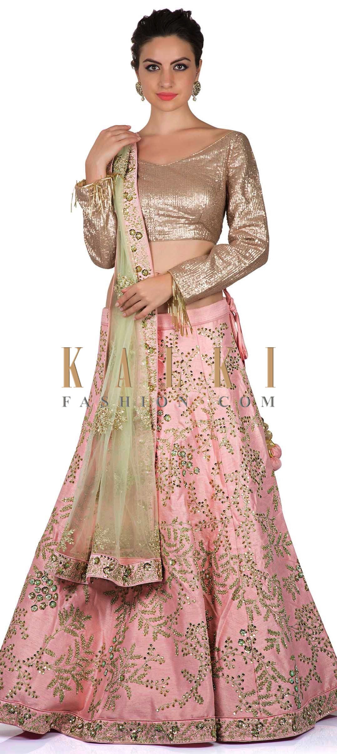 63085c169f998b ‌Baby pink lehenga featuring in silk with zari and kundan embroidery all  over. Matched with sequin blouse in boat neckline with tassel at sleeve end.