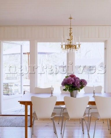 A Modern Scandinavian Style Dining Room With Wooden Dining Table White  Chairs And Mauve Flowers On