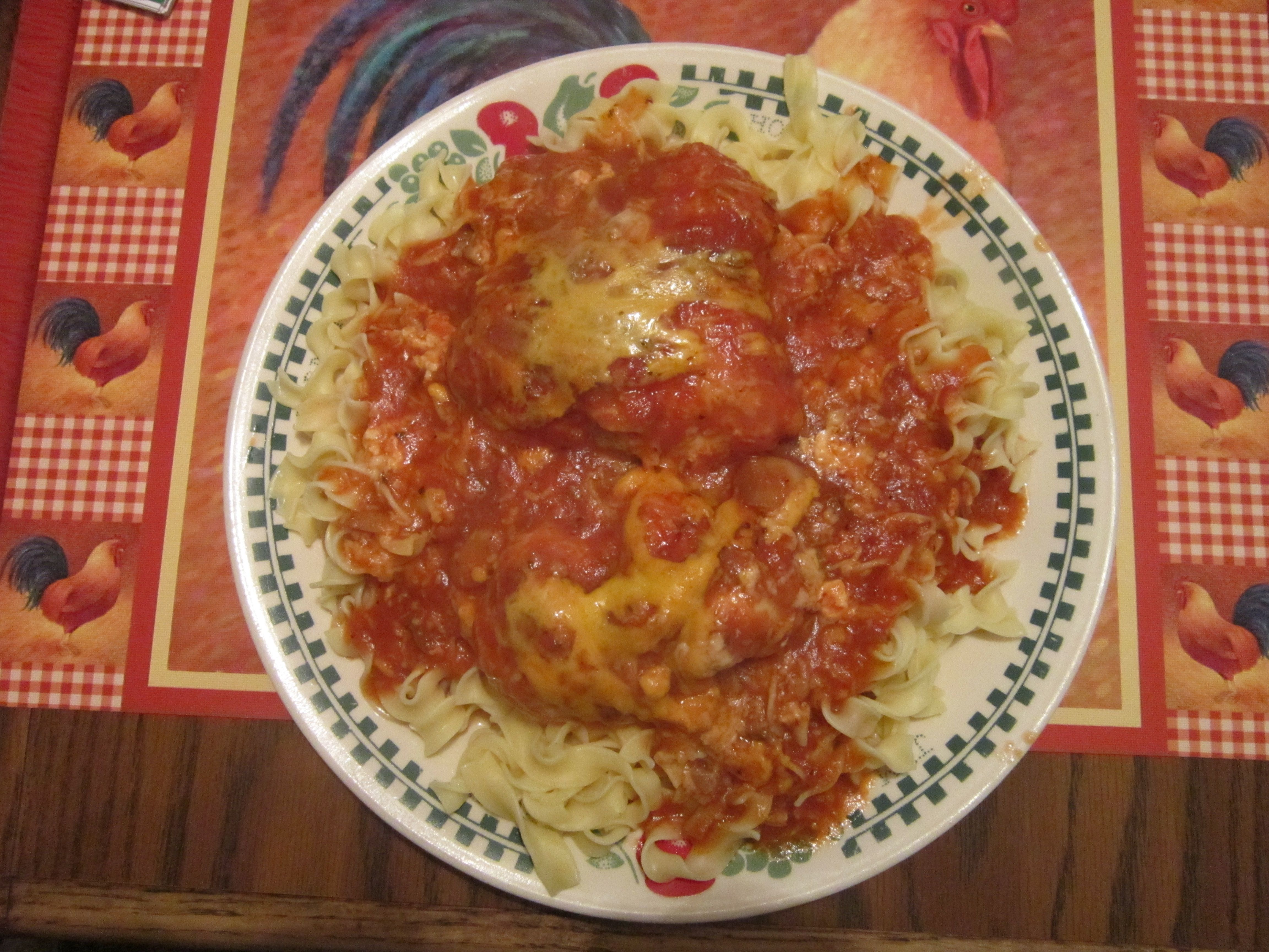 Boneless, skinless chicken breast cooked in Ragu. Seasoned with Italian seasoning and garlic powder. Topped with shredded mozzarella and cheddar cheese. Served over a bed of Egg noodles.