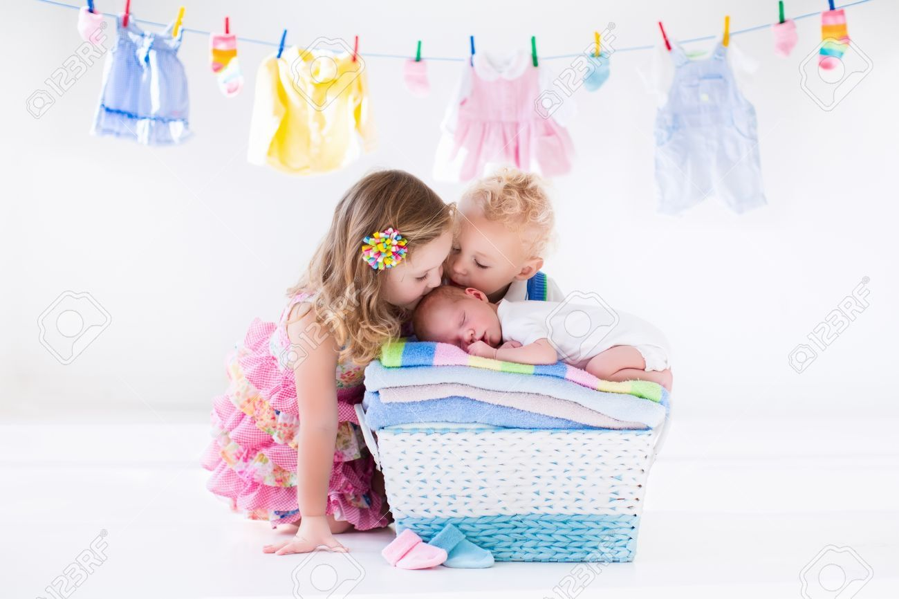Newborn child on a pile of clean dry towels. Brother and sister kissing little sibling. Siblings bonding. Twin toddler kids kiss baby boy. New born kid after bath in a towel. Family washing clothes. Stock Photo , #Ad, #sibling, #kissing, #sister, #Twin, #bonding #bondingwithchild