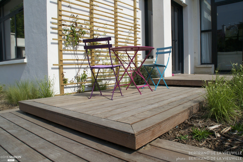 Une terrasse en bois avec chaise de jardin en aluminium coloré.
