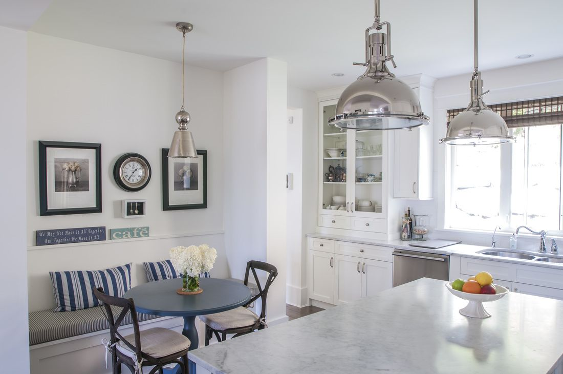 White kitchen cabinets built in eating area chrome pendant lights