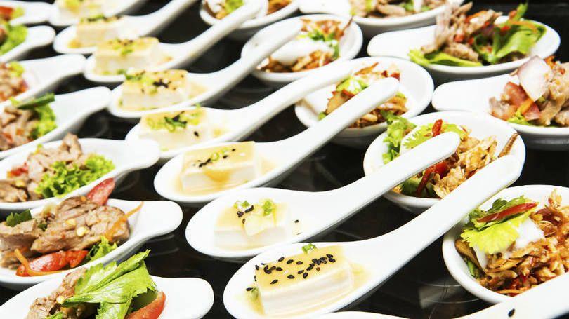 Comidas luxuosas (gourmet) em pequenas colheres em banquete