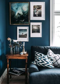 Swedish living room with dark blue marine walls, layered art, and a vintage table