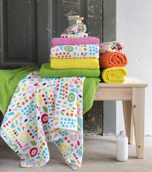 Mehrere Handtücher in kräftigen Farben auf einer Bank aus Holz, u. a. LÖNNERN Badetuch bunt und HÄREN Badetuch leuchtend Gelb.