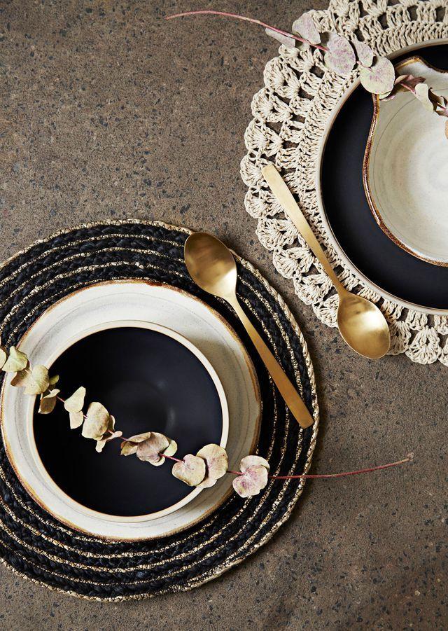 Assiette blanche et marron, 17 x 1,5 cm, 8,78 euros ; bol noir façon poterie, 17,5 x 7,5 cm, 19,59 euros ; assiette noire façon poterie, 15,3 x 2,3 cm, 10,81 euros ; bol blanc et marron, 9 x 4 cm, 9,46 euros ; set de table crochet, beige en papier, 38 cm, 8,78 euros ; set de table noir et or, 40 cm, 6,76 euros, Madam Stoltz