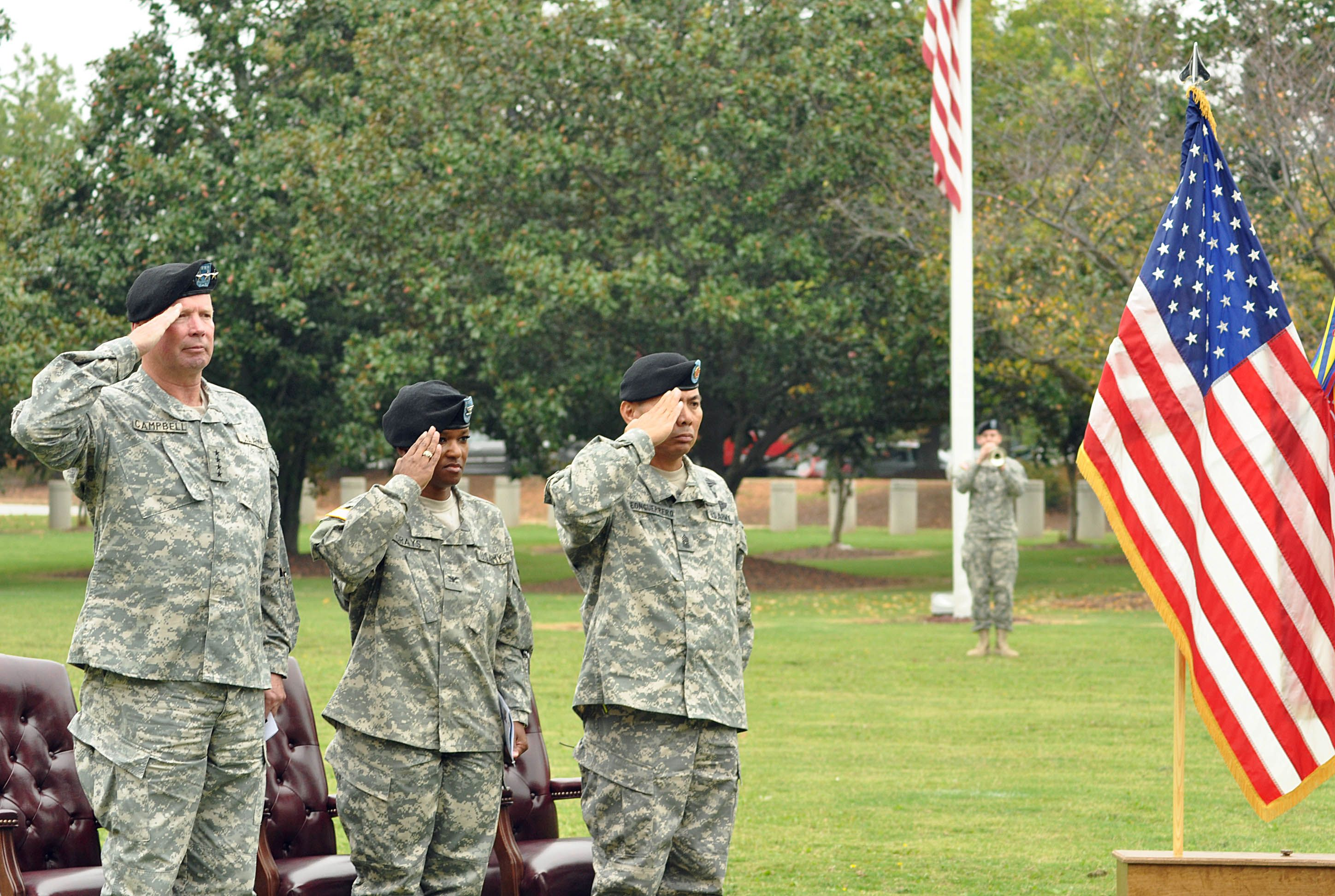 """""""Gen. Charles C. Campbell, U.S. Army Forces commanding general, Col. Deborah B. Grays, U.S. Army Garrison commander and Command Sgt. Maj. Kenny LeonGuerrero, USAG command sergeant major, render salutes to the United States flag as a bugler plays taps during the close of Patriot Day ceremonies held Sept. 11 at Fort McPherson. Fort McPherson and Fort Gillem joined the rest of the nation in honoring the victims of the terrorist attacks that took place Sept. 11, 2001."""" — Wikimedia Commons"""