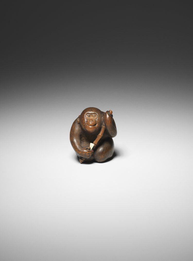 Netsuke. Monkey with stick. Made of wood, with ivory plectrum. Made by: Tomochika 友近 Edo Period Date: Early 19thC Production place: Osaka-fu (Asia, Japan, Honshu, Kansai, Osaka-fu) Materials: wood, ivory Technique: inlaid, carved Height: 3.5 centimetres British Museum number: F.679