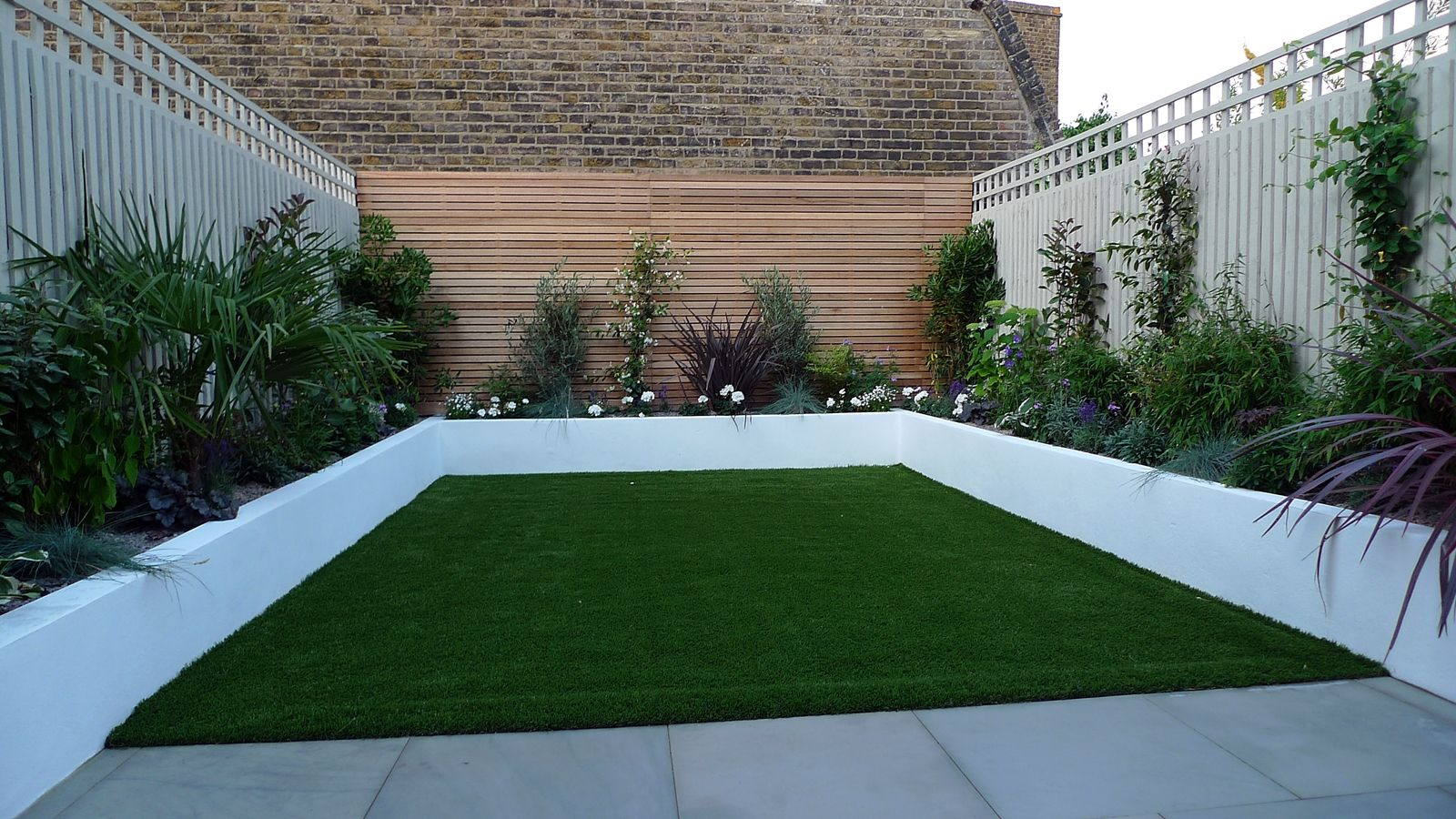 sawn grey sandstone paving raised rendered beds hardwood screen painted stone fence london small garden design