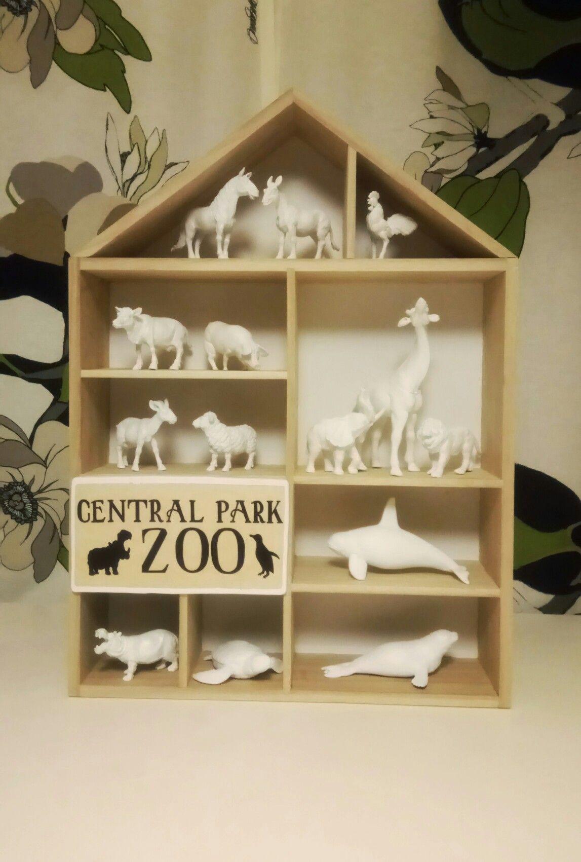 Hyllystä, vanerista ja maalatuista lelueläimistä tehty pikku eläintarha.