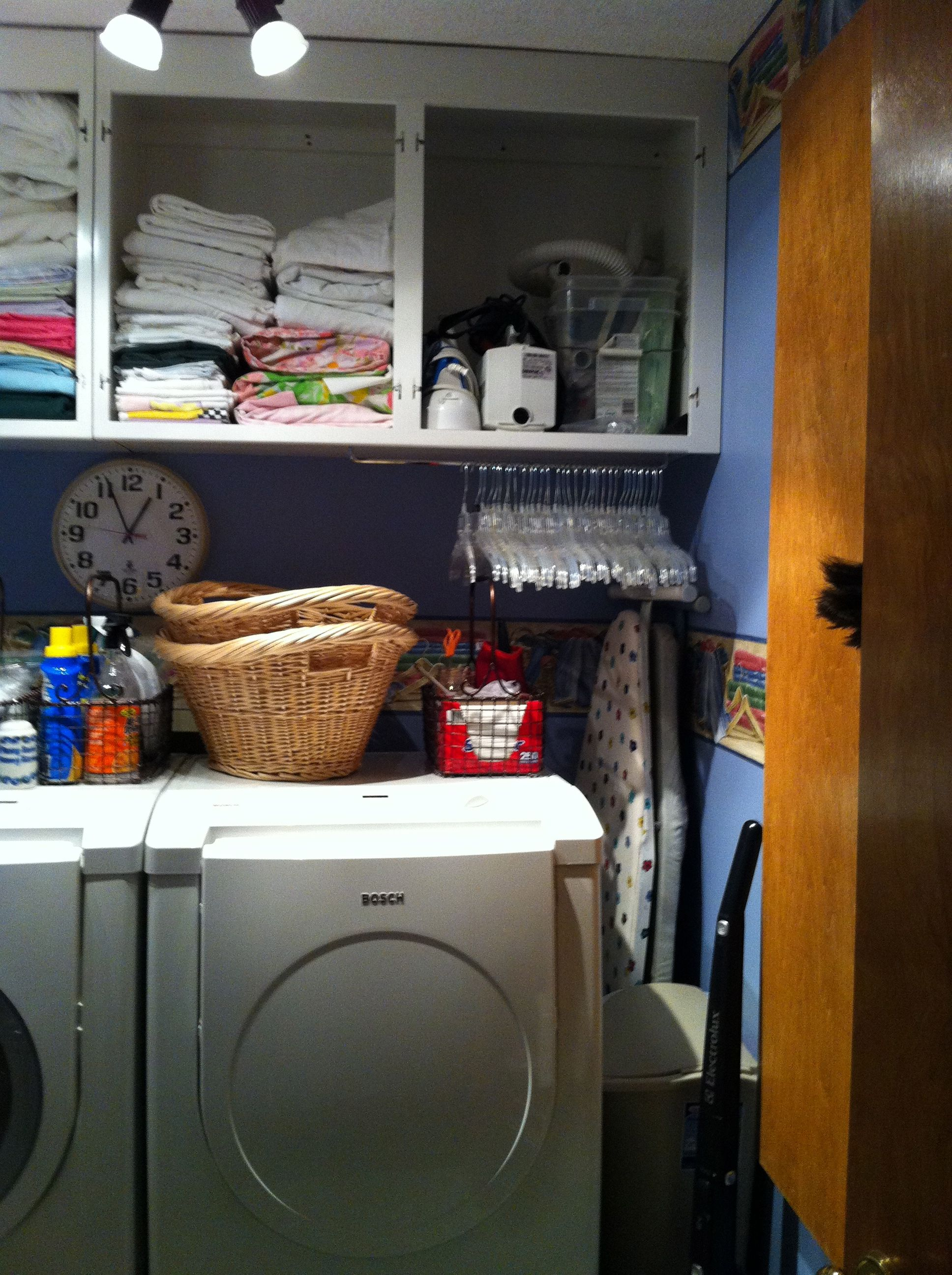 A towel bar mounted underneath a cabinet provides tidy storage for clothes hangers.