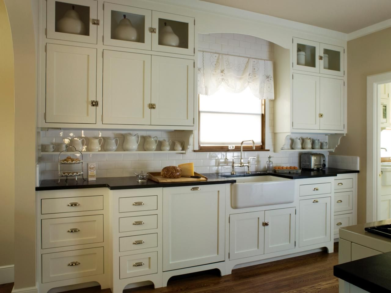 Antique white cabinets kitchen - This Quaint Cottage Kitchen Features Antique White Shaker Cabinets Black Countertops And A White Subway