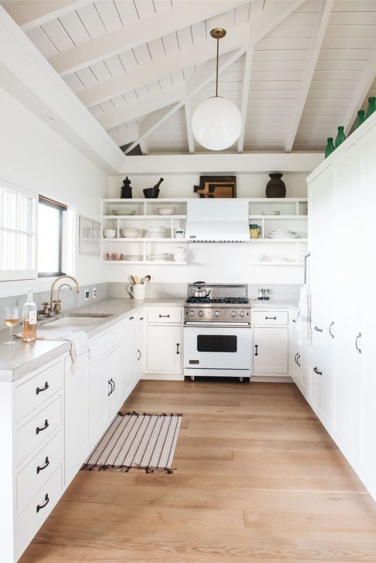 White galley kitchen in a beach house with open shelves vaulted ...