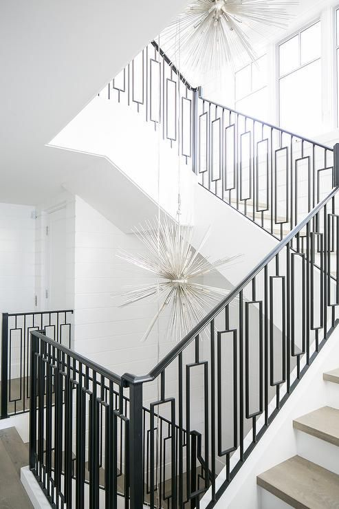 Staggered Silver Sputnik Chandeliers Illuminate A Staircase Fitted With  Gray Treads And Wrought Iron Spindles With