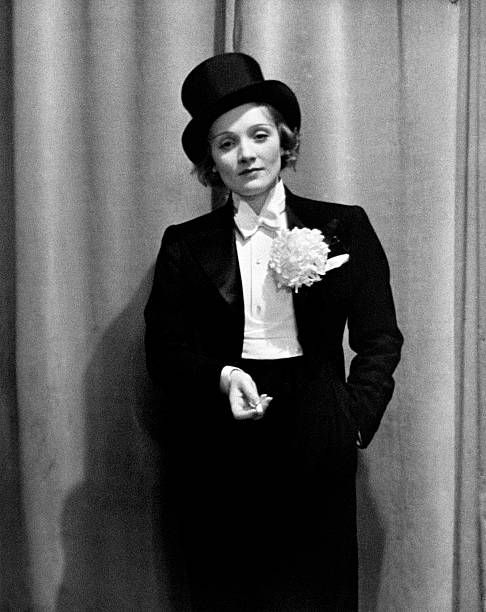 Photo of Actress Marlene Dietrich wearing tuxedo, top hat, corsage and holding…