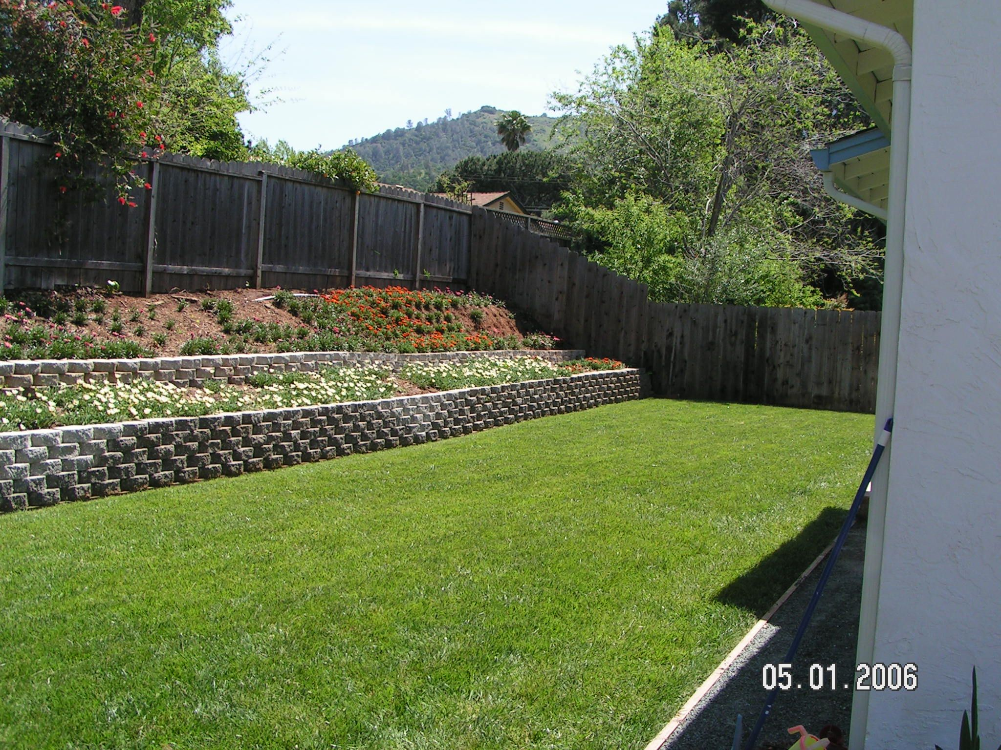 Retaining wall slope down to flat backyard backyard for Backyard garden design