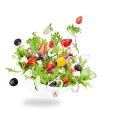 Fresh salad with flying vegetables ingredients stock photo