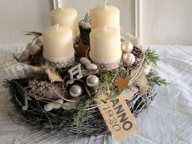 Aufwendig gestalteter Adventskranz bestehend aus einem geweißten Astkranz und einem darauf sitzenden Mooskranz mit vier cremefarbenen Stumpenkerzen, welche mit Baumwollspitze und gepunktetem Band...