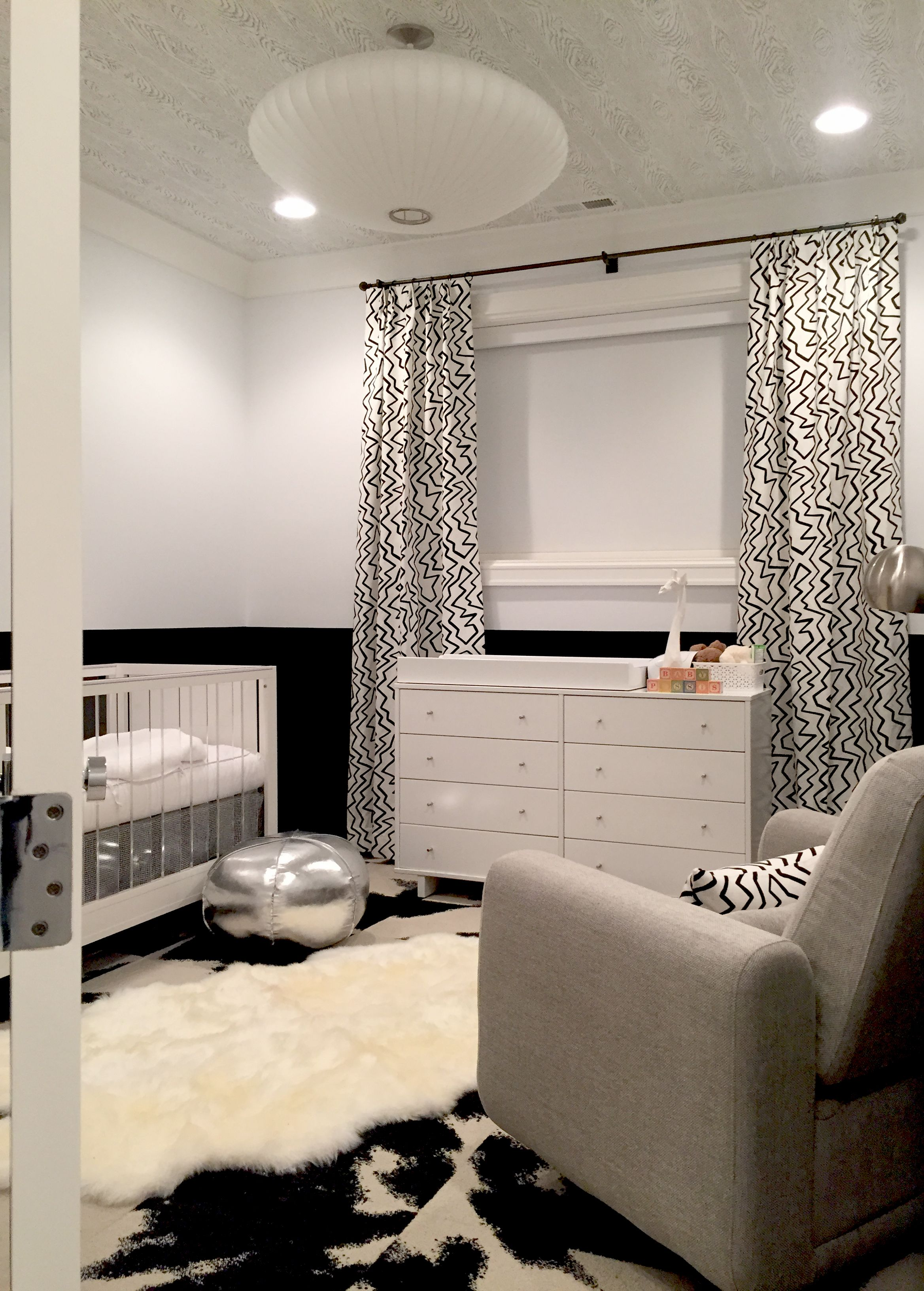 Urban Baby Nursery - black and white, cowhide rug, print fabric from Lee Jofa on custom drapery