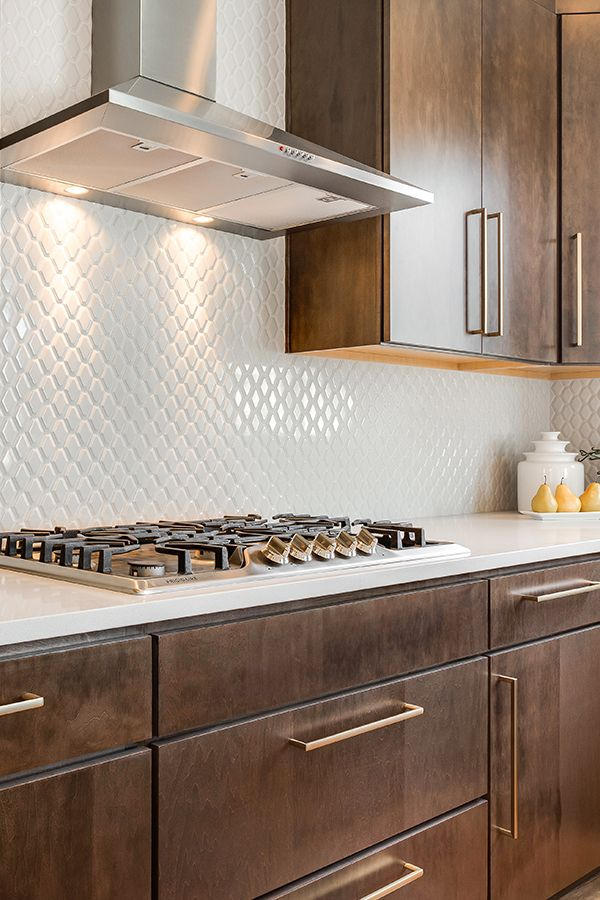 this kitchen is serving serious style white textured backsplash with brown cupboards and gold on kitchen remodel gold hardware id=21425