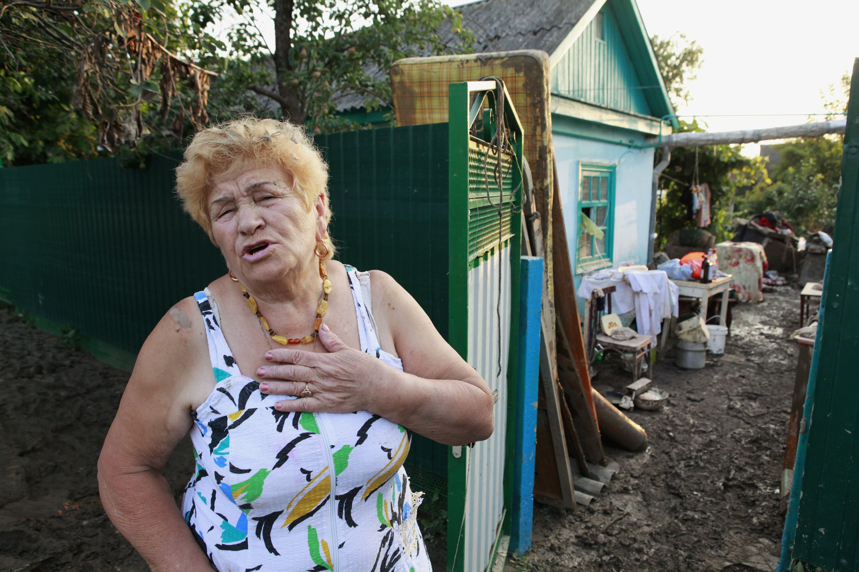 A woman speaks as she stands in a street, hit by floods, in the town of Krymsk