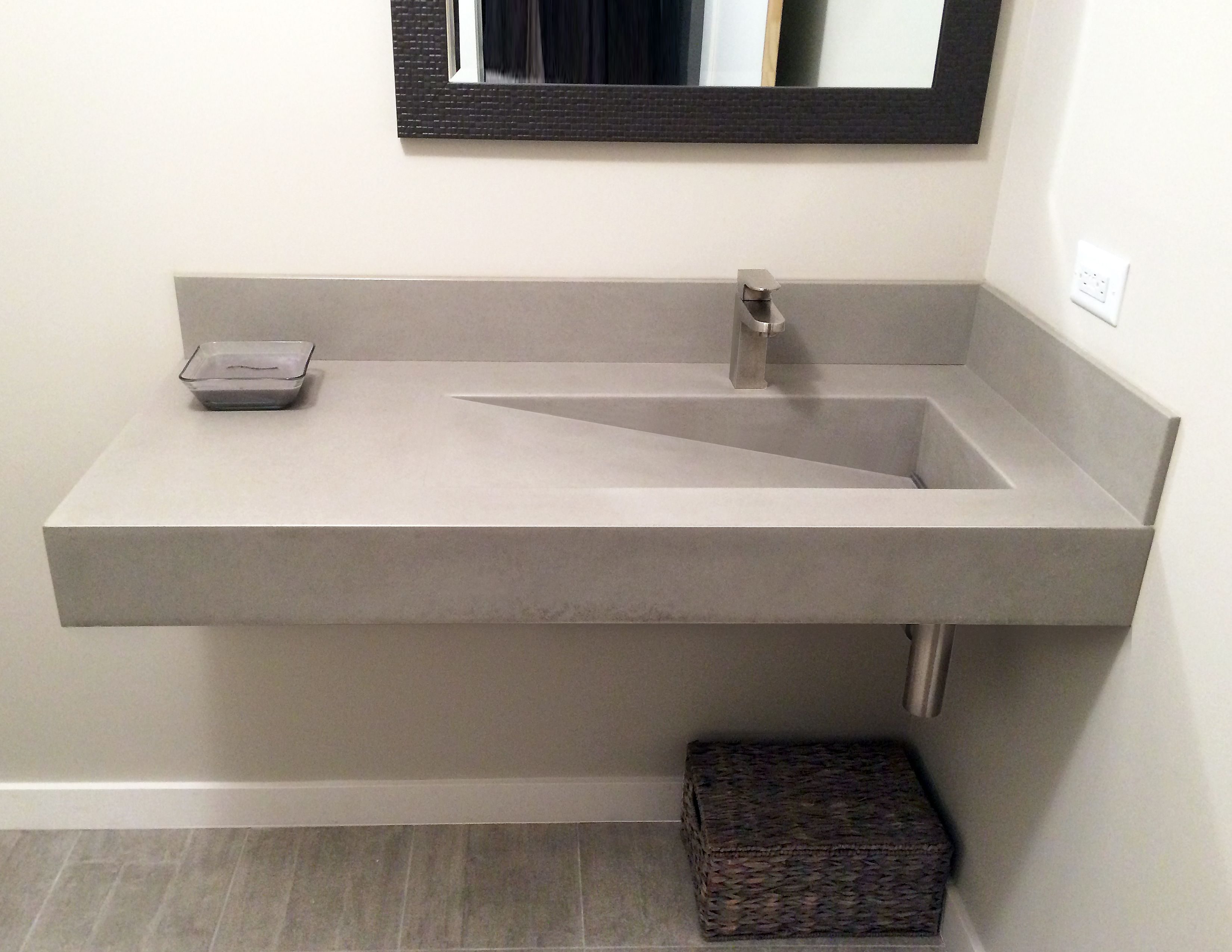 Wall hung concrete bathroom sink with a custom ramp sink by