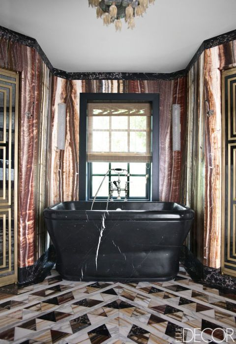Designer Kelly Wearstler incorporated a mixture of luxurious materials in the master bathroom of Lara and Jeff Sanderson's Mercer Island, Washington, home. The walls are covered in onyx fantastico, and the flooring is marble and onyx; the sconces are vintage.: