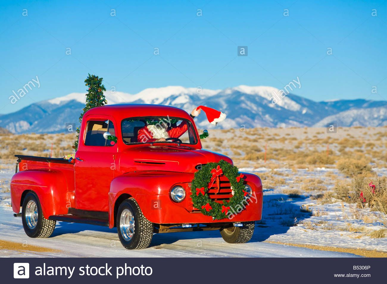 Download this stock image: Santa driving a vintage red Ford pick-up truck down a snowcovered ...