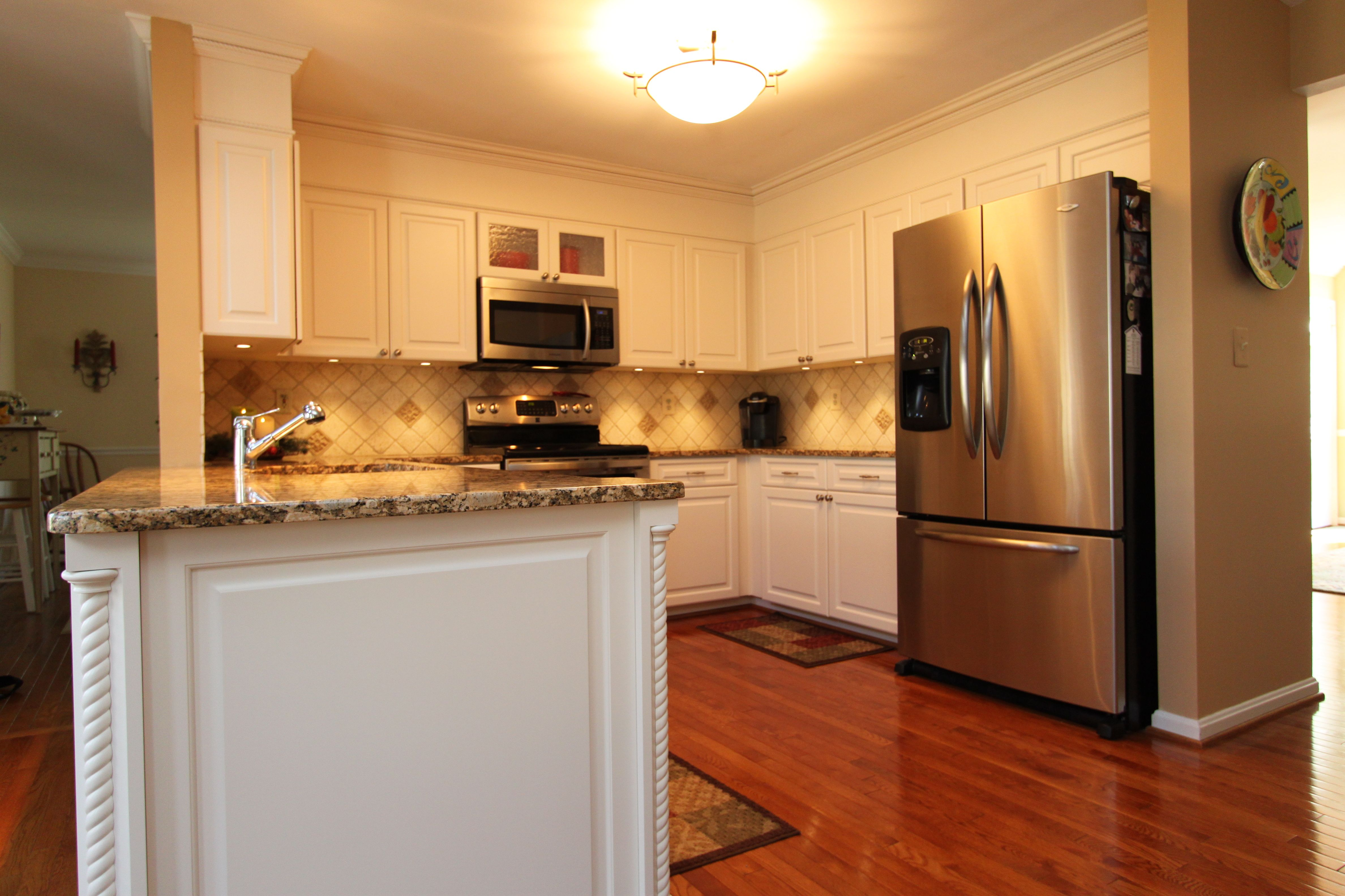transitional style white kitchen with tan granite countertops in