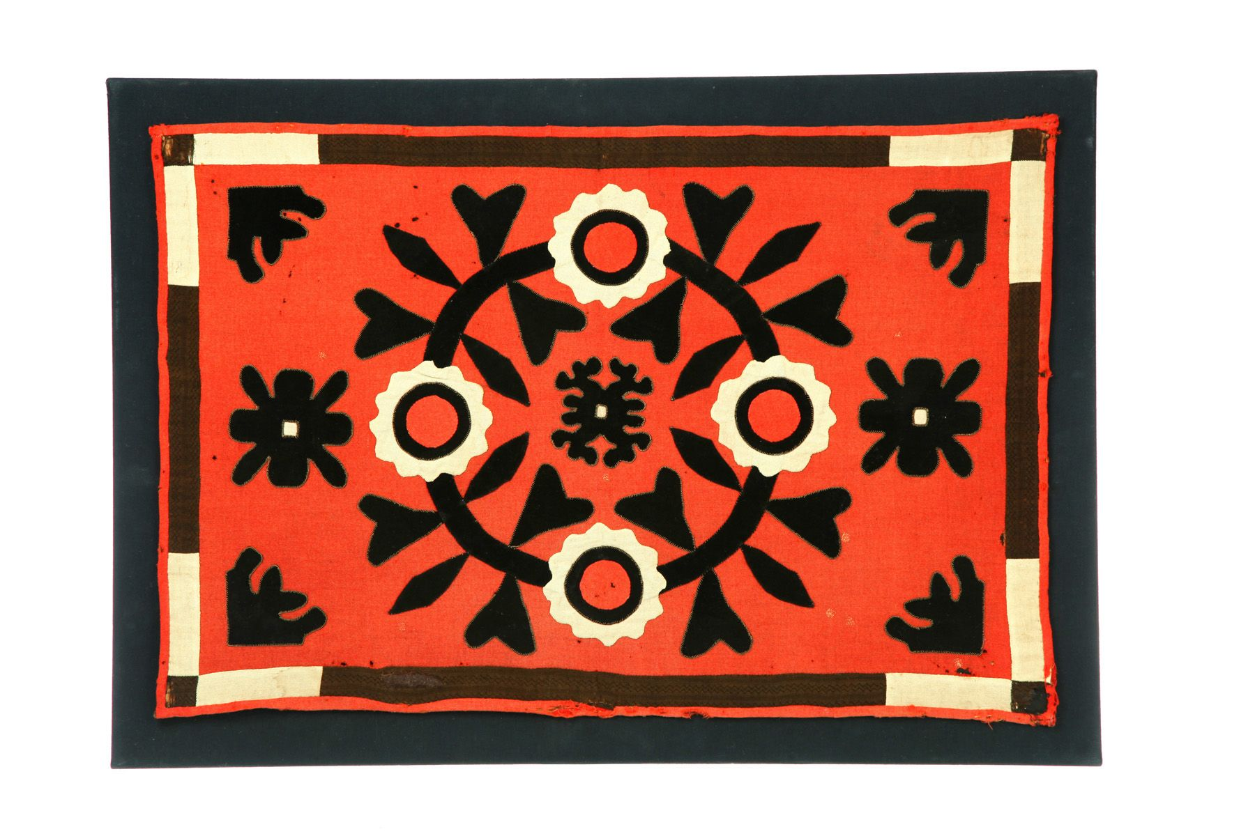 "Table rug, American, mid 19th century, wool and cotton. Appliqued wreath and two-color border, cotton print backing. 21.5"" h. 32.5""w Found in Massachusetts.Sale 1111, Lot 33"