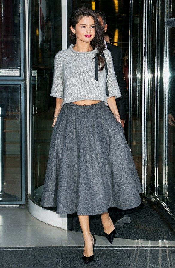 2d0a36526e Selena Gomez wears a cropped sweater, full wool gray skirt, and pointed-toe  pumps