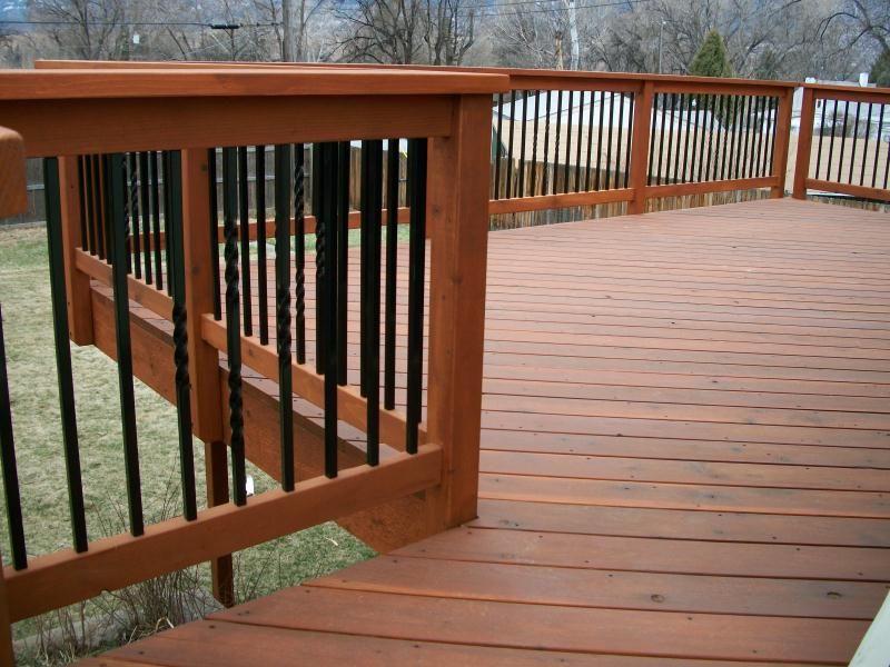 Deck railing balusters redwood color connecting deck for Garden decking banister