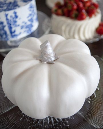 A pumpkin-spice cake filled with honey buttercream icing and covered with white rolled fondant